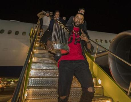 Boston, Ma— October 29, 2018-Stan Grossfeld/ Globe Staff—Eduardo Nunez carried the World Championship trophy off the Red Sox charter on the way back from winning the World Series in Los Angeles.