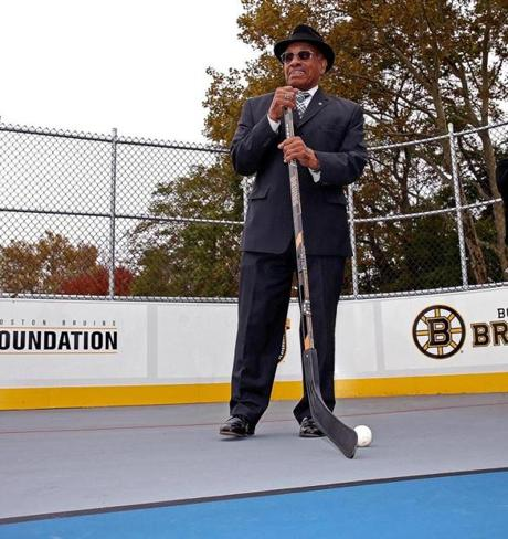 Willie O'Ree standing, and smiling, on the new street hockey rink named after him in Allston.