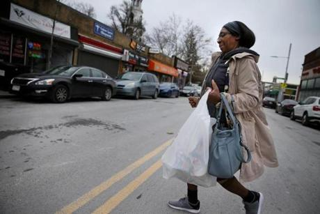 "(FOR KOWALCZYK MEDICAL STORY) Boston, MA - November 21, 2018: Marie Cajuste, 58, hurries across Washington Street while shopping in Codman Square in the Dorchester neighborhood of Boston. She says she tries not to worry about crime in the neighborhood, despite a recent shooting in front of her boarding house.""I do my thing and come home. If something happens in the neighborhood, it's not me."" (Craig F. Walker/Globe Staff) section: metro reporter: Kowalczyk OR (FOR KOWALCZYK MEDICAL STORY) Boston, MA - November 21, 2018: Marie Cajuste, 58, hurries across Washington Street while grocery shopping in Codman Square in the Dorchester neighborhood of Boston. She had stopped cooking during the most intense part of her cancer treatment because she was exhausted but recently returned to the kitchen. (Craig F. Walker/Globe Staff) section: metro reporter: Kowalczyk"