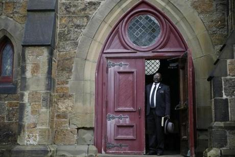 A deacon poked his head out of the entrance to the Eliot Congregational Church of Roxbury.