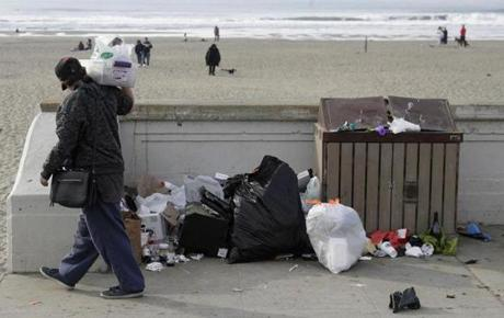 A woman walked past trash piled next to a garbage bin at Ocean Beach in San Francisco. Nonprofits, businesses and state governments across the country are paying bills and putting in volunteer hours in an uphill battle to keep national parks safe and clean for visitors.