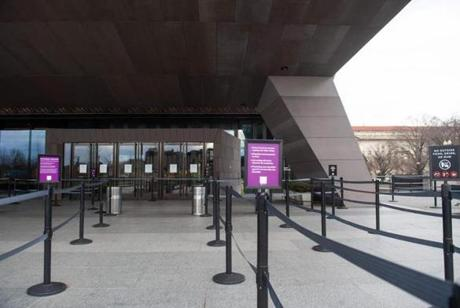 An empty entrance line is seen as signs hung on the doors of the Smithsonian National Museum of African American History and Culture tell visitors that the museum is closed.