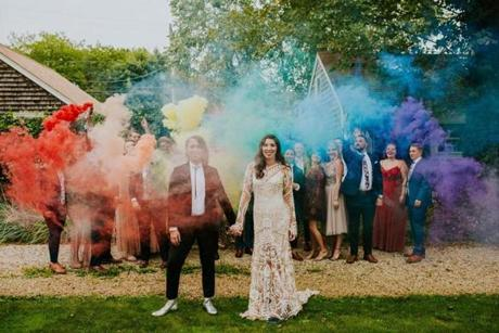 PHOTO CREDIT; NATO TUKE  Jess Mooney and Katy DeMoura declare their pride in front of an installation of rainbow-colored smoke before tying the knot.