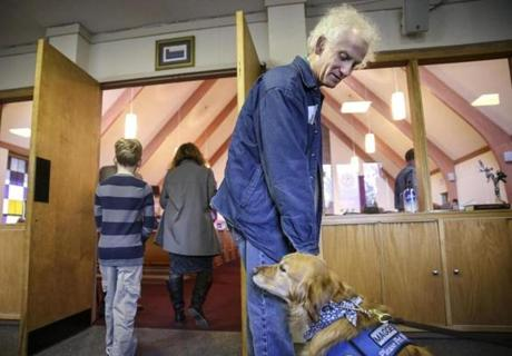 Gordon Thompson pets Maggie, a 7-year-old golden retriever comfort dog, before a Sunday service at Christ the King Lutheran Church in Newtown, Conn.