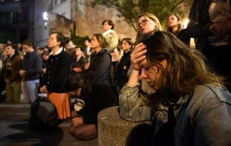 People kneel on the pavement as they pray outside watching flames engulf Notre Dame Cathedral in Paris on April 15, 2019. - A colossal fire swept through the famed Notre Dame Cathedral in central Paris on April 15, 2019, causing a spire to collapse and raising fears over the future of the nearly millenium old building and its precious artworks. The fire, which began in the early evening, sent flames and huge clouds of grey smoke billowing into the Paris sky as stunned Parisians and tourists watched on in sheer horror. (Photo by ERIC FEFERBERG / AFP)ERIC FEFERBERG/AFP/Getty Images