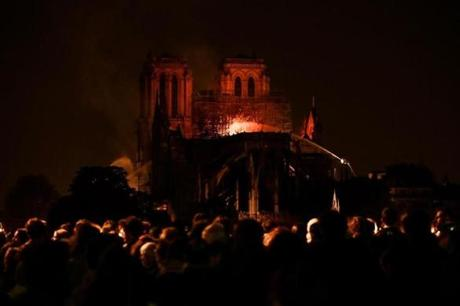 Bystanders look on as flames and smoke billow from the roof at Notre Dame Cathedral in Paris on April 15, 2019. - A major fire broke out at the landmark Notre Dame Cathedral in central Paris sending flames and huge clouds of grey smoke billowing into the sky, the fire service said. The flames and smoke plumed from the spire and roof of the gothic cathedral, visited by millions of people a year, where renovations are currently underway. (Photo by FRANCOIS GUILLOT / AFP)FRANCOIS GUILLOT/AFP/Getty Images