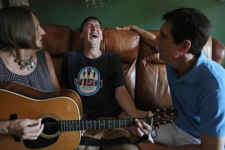 "Cambridge, MA., 07/03/2019, Pat and Tammy McLeod, and their son Zack. In this photo Zack and his mother play the guitar and sing together. The parents are two chaplains at Harvard UNiversity. They have written a book about the experience of their sons' traumatic brain injury. The book, ""Hit Hard,"" tells the story of their son, Zach, who lost most of the use of his brain when he was hit during a football scrimmage in 2008. The book is part of a larger conversation about how to grieve ""ambigous loss"" and also the national conversation about football-related injuries. Pat, a former football player, isn't ready to write off the sport quite yet; his wife, Tammy, can't bring herself to watch another game and thinks that colleges and other schools should end the sport entirely. Suzanne Kreiter/Globe staff"