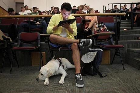 Worcester, MA., 09/13/2019, Jack Duffy-Protentis and his service dog, Adonis, in class together at WPI. Jack was in the third grade when he learned he had a degenerative eye disease that would limit his vision for the rest of his life. He is now a senior studying mechanical engineering at Worcester Polytechnic Institute in Worcester, Massachusetts. The rapid progression of his vision has not stopped his can-do attitude. Jack grew up in Easton, Massachusetts and while a junior and senior in high school, Jack was the Captain of the Oliver Ames Iron Tigers Robotics Team. During his tenure, the Iron Tigers competed in the nationals in St. Louis, Missouri. Suzanne Kreiter/Globe staff