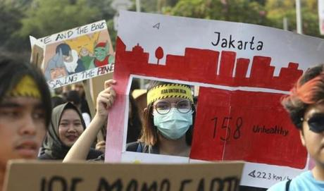 An activist holds up a poster depicting Jakarta's air quality during a climate change rally in Jakarta, Indonesia Friday, Sept. 20, 2019. Hundreds of protestors gathered in response to a day of worldwide demonstrations calling for action to guard against climate change. (AP Photo/Achmad Ibrahim)