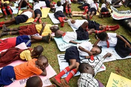 School children lie on the grass as they take part in a rally, part of the global climate walk 2019, against climate change in Wakiso, on September 20, 2019. - Children across Asia and the Pacific kicked off what are set to be the largest global climate protests in history on September 20, 2019, demanding adults act now to stop environmental disaster. From Sydney to Seoul, Manila to Mumbai, children heeded the rallying cry of fellow teen activist Greta Thunberg and shut their textbooks in a collective call to action. (Photo by ISAAC KASAMANI / AFP)ISAAC KASAMANI/AFP/Getty Images
