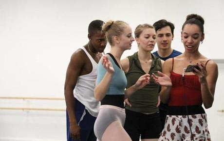 "Boston, MA 9/10/19 Boston Ballet dancer Chyrstyn Fentroy (cq), right, runs a rehearsal of her choreographed piece, ""you,"" (cq) in the ballet's studio. She shows a video of the steps to dancers, from left, Tyson Clark (cq), Molly Novak (cq), Ryan Kwasniewski (cq), and Nations Wilkes-Davis (cq). (The piece, for seven dancers, is set to ""Danse Macabre"" in G Minor, Op.40, by Camille Saint-Saëns (cq). It will be performed later in October as part of BB@home: ChoreograpHER (cq). Photo by Pat Greenhouse/Globe Staff Topic: 22Fentroy Reporter: Marella Gayla"