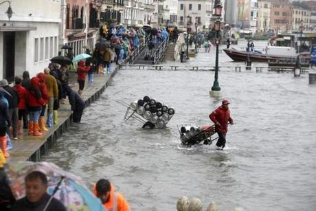 People walked on raised platforms while others pushed goods through the high tide flooding.