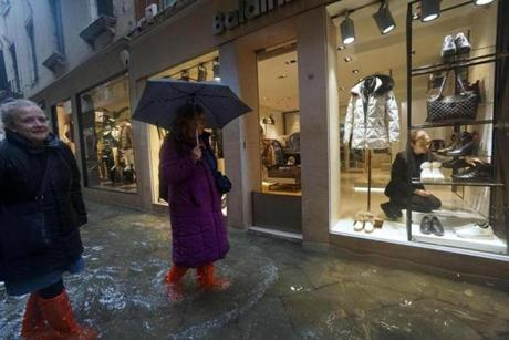 A shop assistant adjusts shoes as women outside wade through a flooded street on the occasion of a high tide, in Venice, Italy, Tuesday, Nov. 12, 2019. The high tide reached a peak of 127cm (4.1ft) at 10:35am while an even higher level of 140cm(4.6ft) was predicted for later Tuesday evening. (Andrea Merola/ANSA via AP)