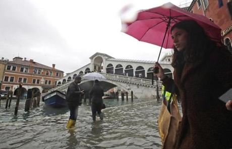 People walked in water near the Rialto bridge during high tide.