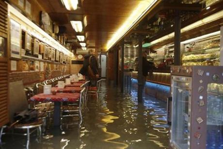 People stood inside a flooded Venetian cafe during high tide.