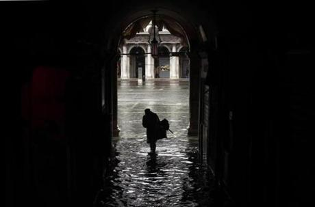 A woman walked toward a flooded St. Mark's Square.