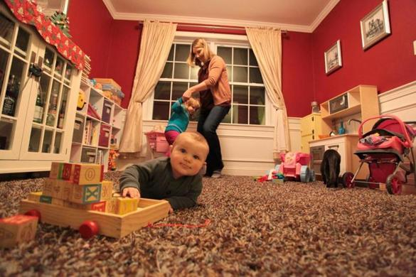 Kate Lynde plays with her children Aria, 3, and Coen, 8 months, in the dining room of their Tewksbury home.