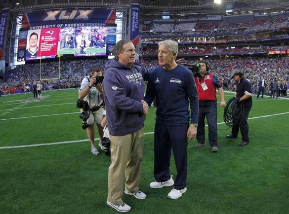 New England Patriots head coach Bill Belichick (L) and Seattle Seahawks head coach Pete Carroll meet at center field during warm-ups ahead of the NFL Super Bowl XLIX football game in Glendale, Arizona February 1, 2015. REUTERS/Brian Snyder (UNITED STATES - Tags: SPORT FOOTBALL)