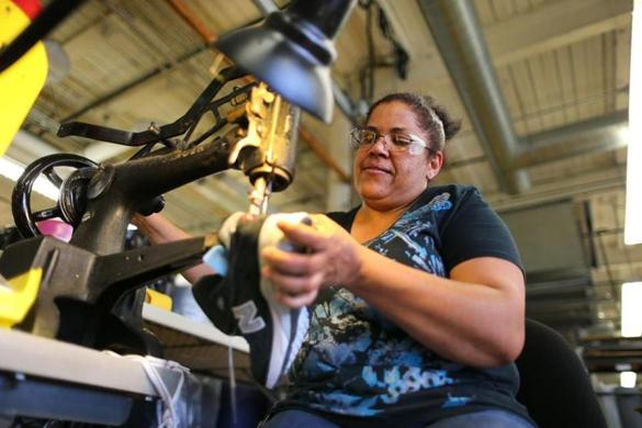 Eddy Maria Taveras used a hand-crank Singer sewing machine to make a repair on a running shoe at the New Balance factory in Lawrence.