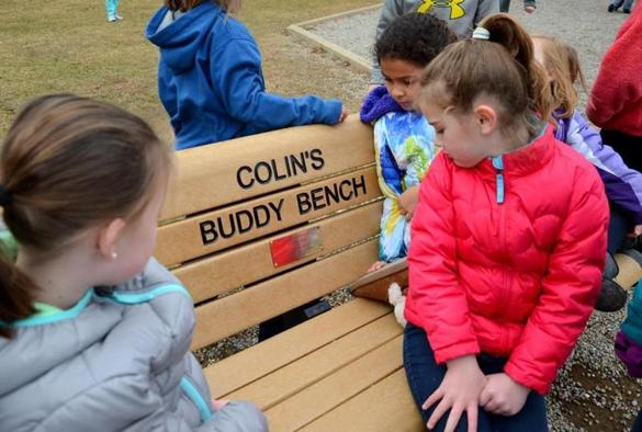 Olivia Craig, 7, right, on the Buddy Bench near the playground area at the Thomas W. Hamilton School in Weymouth. Children can sit on the bench when they feel left out and want a friend to play with.