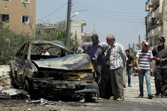 Civilians inspect a burnt car at a site hit by an airstrike in the rebel-controlled city of Idlib, Syria June 29, 2016. REUTERS/Ammar Abdullah