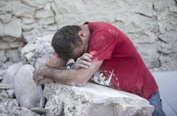 A man leaned on the rubble of buildings in Amatrice, Italy, destroyed in Wednesday's earthquake.
