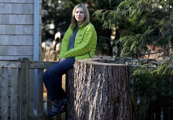 Beverly Farms Ma- 12/20//2016 A developer has cut down 14 mature trees including a 75 year old maple . The tree's were abutting along Nathalie Majorek's ,side of a private driveway. Nathalie, is sitting atop stump of a red maple that was cut down. Jonathan Wiggs /GlobeStaff) Reporter:Topic