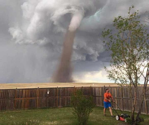 Theunis Wessels mowed his lawn at his home in Three Hills, Alberta, as a tornado swirled in the background.