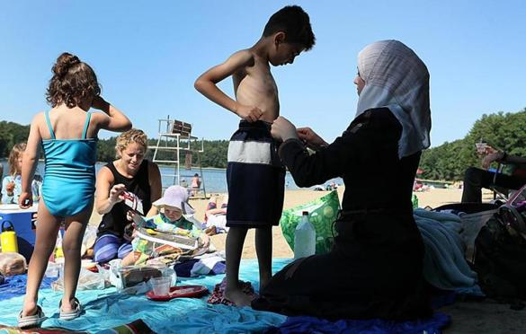 NOT FOR GETTY. Concord, Ma., 07/16/17, Asmaa helps her son, Ali, with his swim suit at Walden Pond---her first visit to an American beach. Suzanne Kreiter/Globe staff