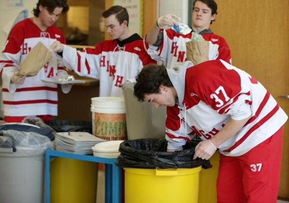 Members of the Hingham High School hockey team sorting out what their schoolmates threw out after lunch in the school cafeteria.