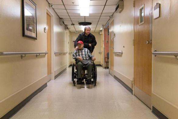 Nick Bonanno pushed his father, Russ Bonanno, down the hallway at the VA in Bedford.
