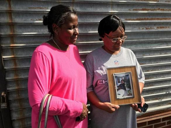 Mayra Cardona (left) and Rosa Phinn-Westby with a photo of their brother, Jose Luis Phinn Williams, who they identified as the gas station attendant fatally shot in Dorchester last month.