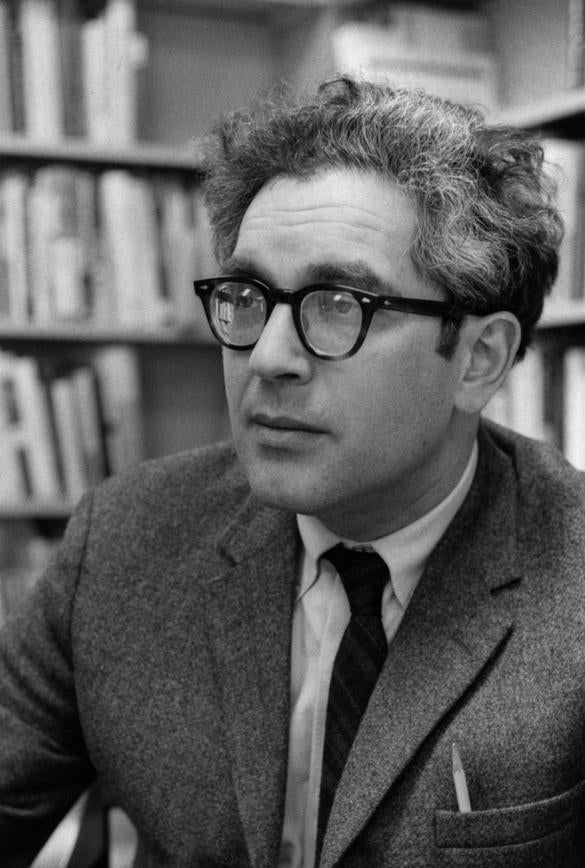 Head-shot portrait of American sociologist Nathan Glazer, seated in a library, wearing a dark suit, with a pencil poking out of his jacket packet, wearing thick, dark glasses, with a serious facial expression, 1969. (Photo by JHU Sheridan Libraries/Gado/Getty Images).