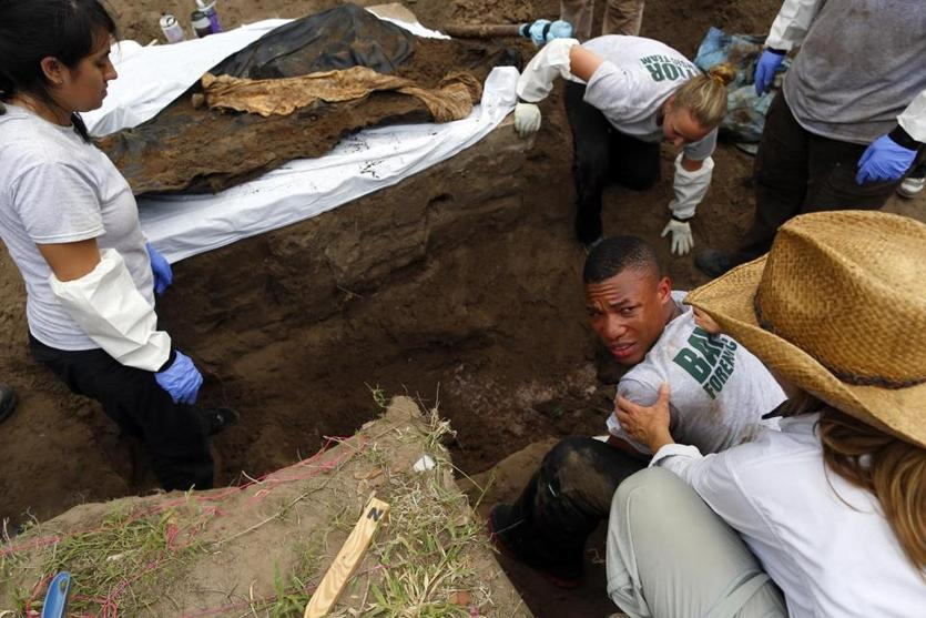 Xavier Colbert, 22, a Baylor senior, was helped by a professor as he lifted a body out of a grave. He is part of a team of forensics students working to exhume bodies of unidentified migrants.