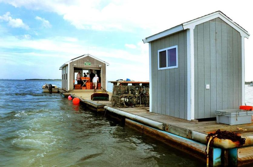 Workers for Island Creek Oysters in Duxbury sort oysters aboard their floating hut.