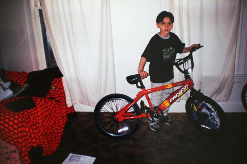 Marco, about 11 years old, poses with a brand-new bicycle Jaime bought for him. Jaime repeatedly gave Marco gifts, often expensive items like video games and a cellphone.