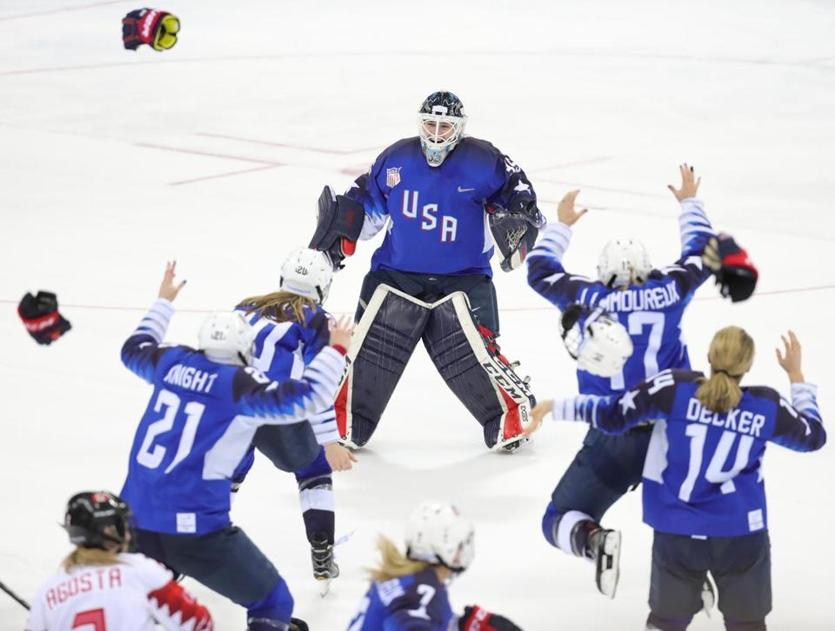Jubilant members of Team USA skate toward Rooney to start the gold-medal party.