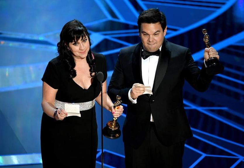 Songwriters Kristen Anderson-Lopez (left) and Robert Lopez accept Best Original Song for 'Remember Me' from 'Coco' onstage.