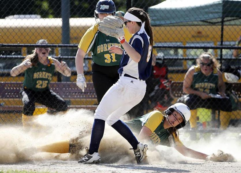 North Reading's Julia Howse slides home safely after a wild pitch by Arlington Catholic's Madison Figueredo.