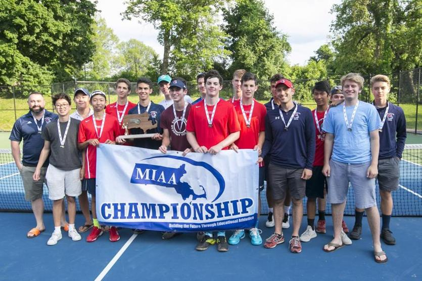 The Brookline boys' tennis team proudly displays the championship trophy and flag.