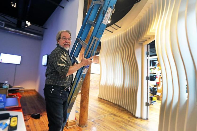 Lawrence, MA 01-08-19: Dennis Hlynsky (cq), carries a ladder he was using to adjust the lighting on his video installation (behind him) as part of an exhibit about crows at the Essex Art Center. (Jim Davis/Globe Staff)