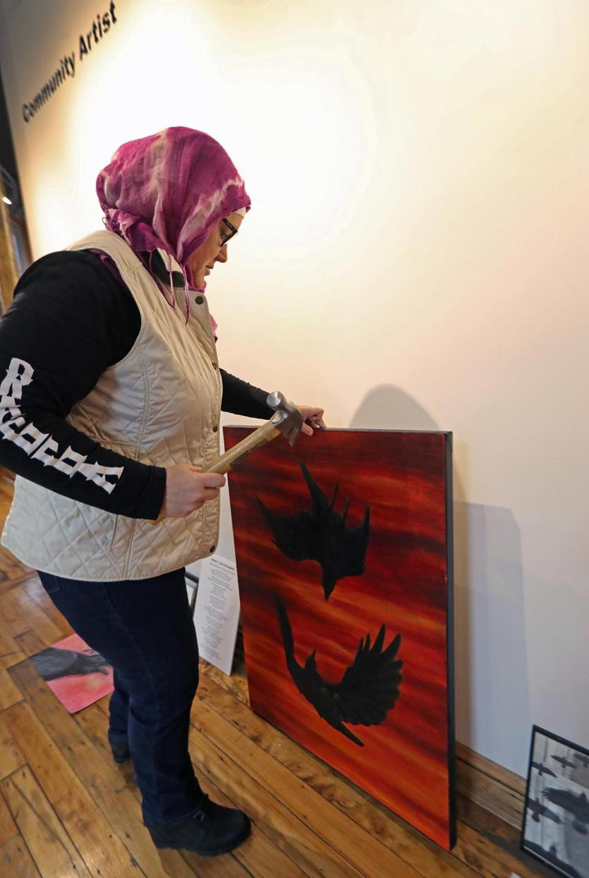 "Lawrence, MA 01-08-19: Anne Thiam, a board member of the Essex Art Center, works on hanging a piece on the ""Community Artist"" wall as part of an exhibit about crows at the Essex Art Center. The oil on canvas painting by Eric Allshouse is titled ""Crow Fight.""(Jim Davis/Globe Staff)"