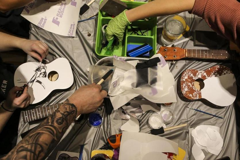 Attendees worked diligently at personalizing their ukuleles during a ukulele-building event put on by Yaymaker at Bertucci's Thursday night. (Nathan Klima for The Boston Globe)