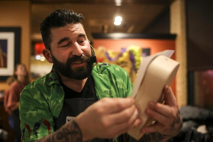 David Daykin demonstrates part of the ukelele building process during a ukulele-building event put on by Yaymaker at Bertucci's Thursday night. (Nathan Klima for The Boston Globe)