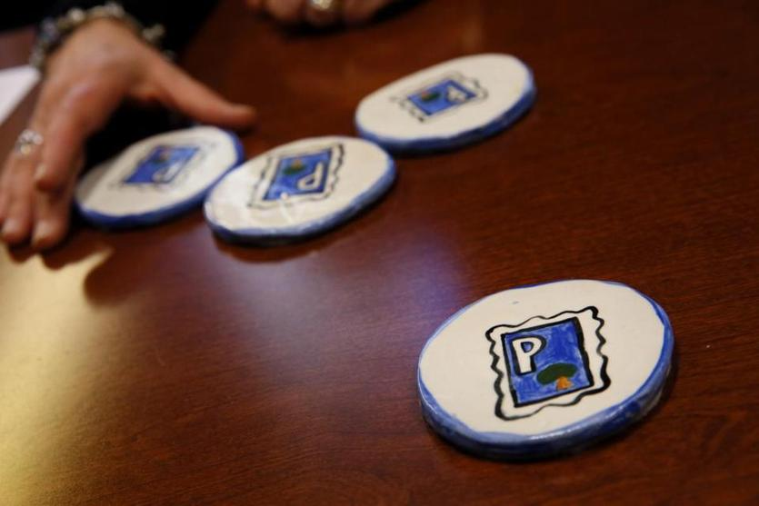 Boston, MA - February 06, 2019: Pamela Messenger, general manager of Friends of Post Office Square displays a set of coasters made by her daughter in her office in Boston, MA on February 06, 2019. The coasters display the Friends of Post Office Square logo and were a gift from her daughter Olivia Messenger in 2007 when she started the job. (Craig F. Walker/Globe Staff) section: Metro reporter: