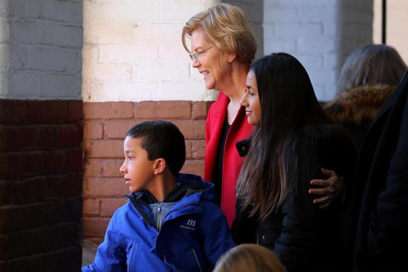 Warren looked at the crowd with her grandchildren, Atticus and Lavinia Tyagi.