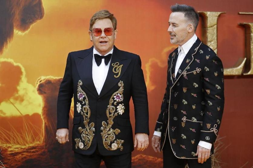 TOPSHOT - English singer-songwriter Elton John (L) and his husband Canadian producer David Furnish (R) pose on the red carpet upon arriving for the European premiere of the film The Lion King in London on July 14, 2019. (Photo by Tolga AKMEN / AFP)TOLGA AKMEN/AFP/Getty Images