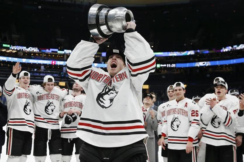 Northeastern goalie Craig Pantano holds up the trophy after Northeastern defeated Boston University in double overtime during the Beanpot Tournament championship NCAA college hockey game in Boston, Monday, Feb. 10, 2020. (AP Photo/Michael Dwyer)