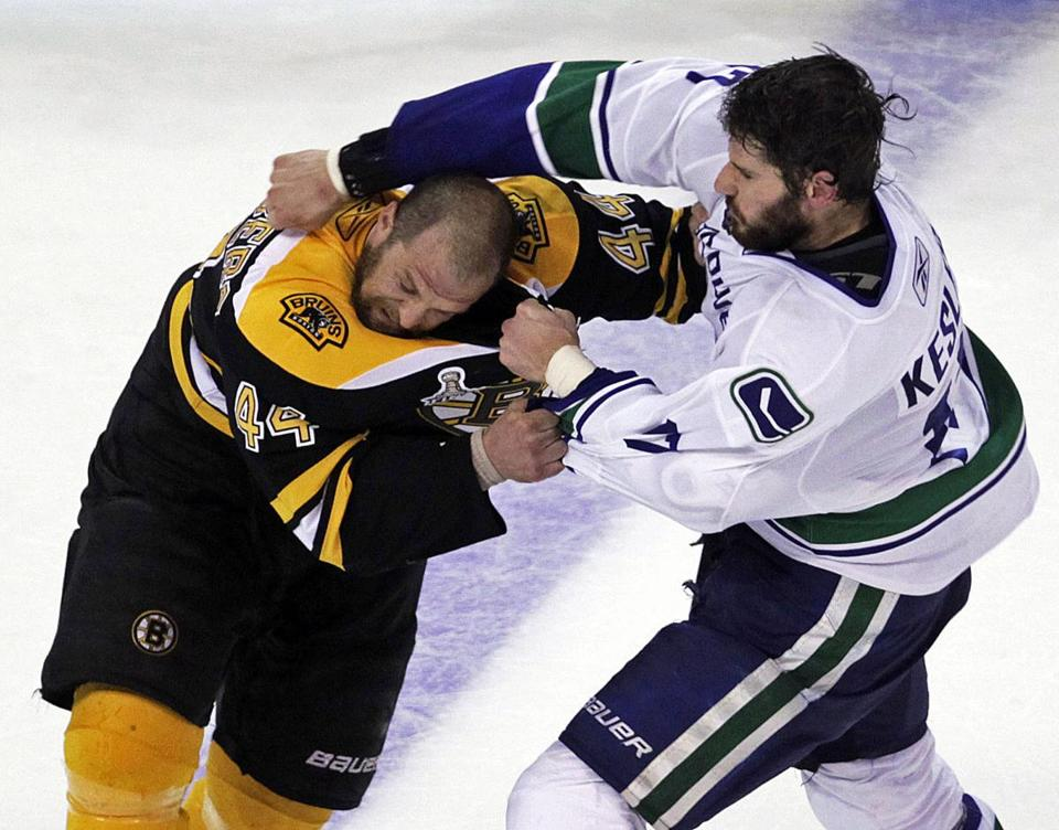 Dennis Seidenberg and Vancouver's Ryan Kessler engage in a third-period fight.