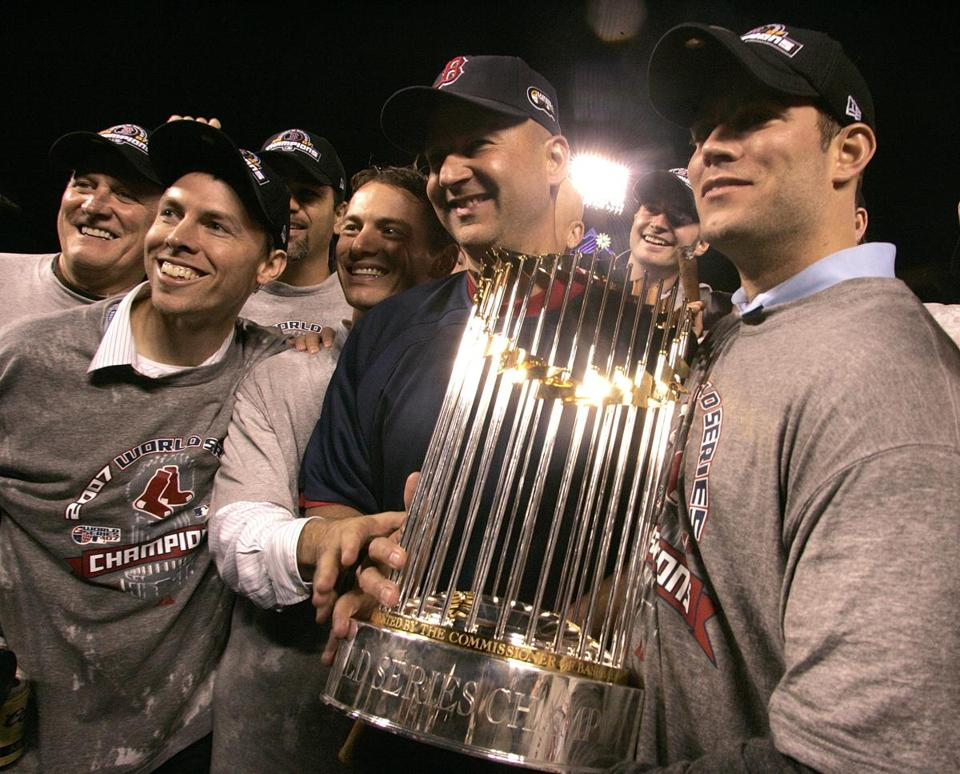 Former Red Sox manager Terry Francona and former GM Theo Epstein, pose with the World Series trophy in 2007.